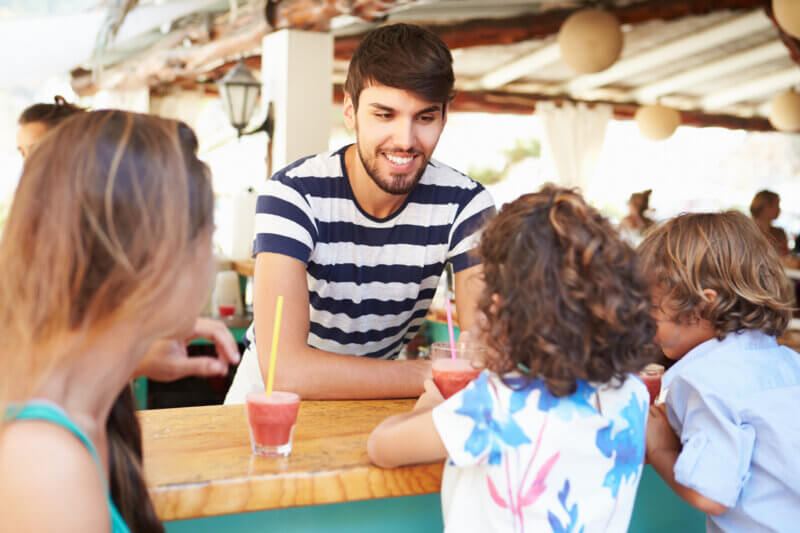 Bartender handing mocktails to young children and mother