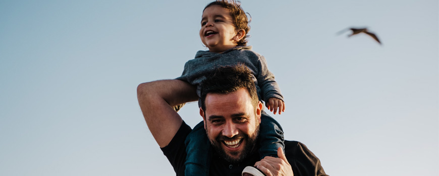 Young child smiling while his father holds him on top of his shoulders.