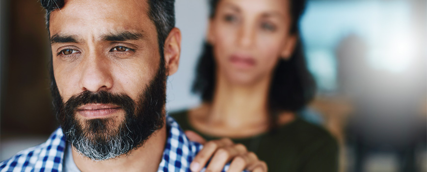 Woman placing hand on man's shoulder offering emotional support.