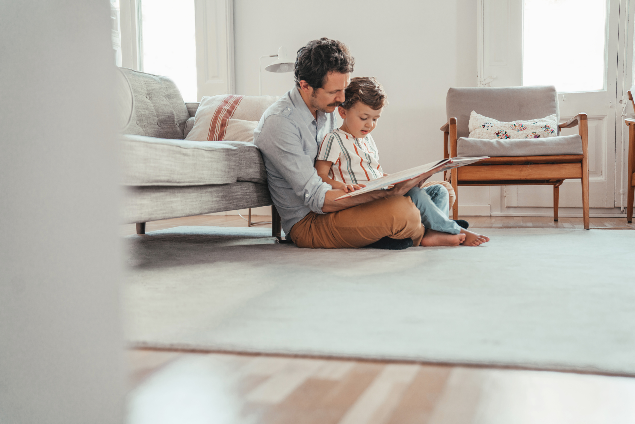 Father reading to his son on the floor of their living room