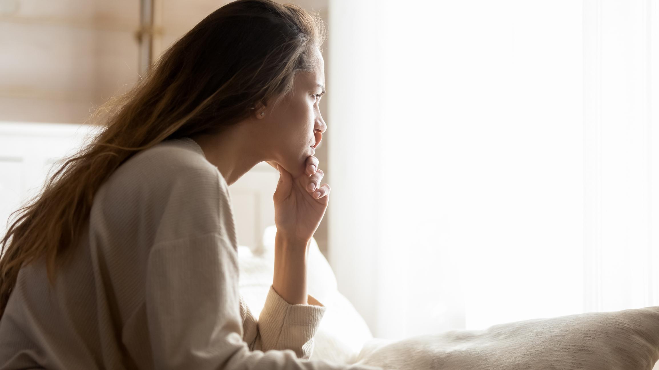 upset women looking at her bedroom window