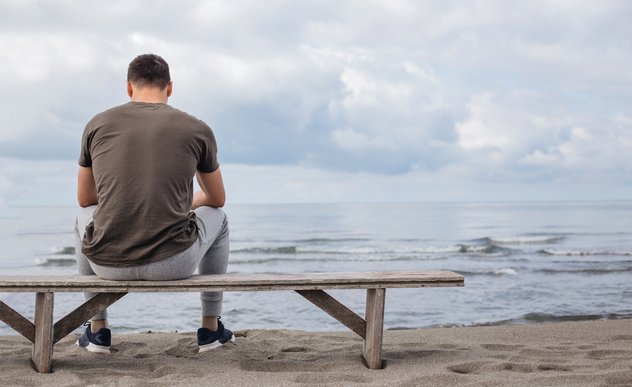 Man sitting on a bench at the beach by himself