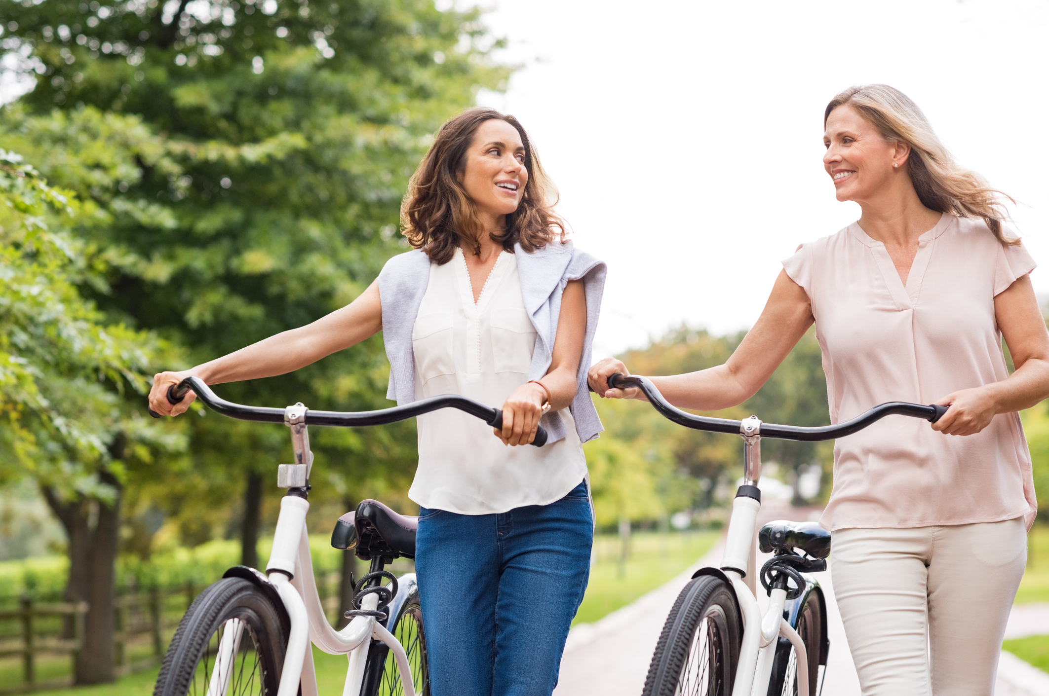 two women walking thier bikes outside taking to each other