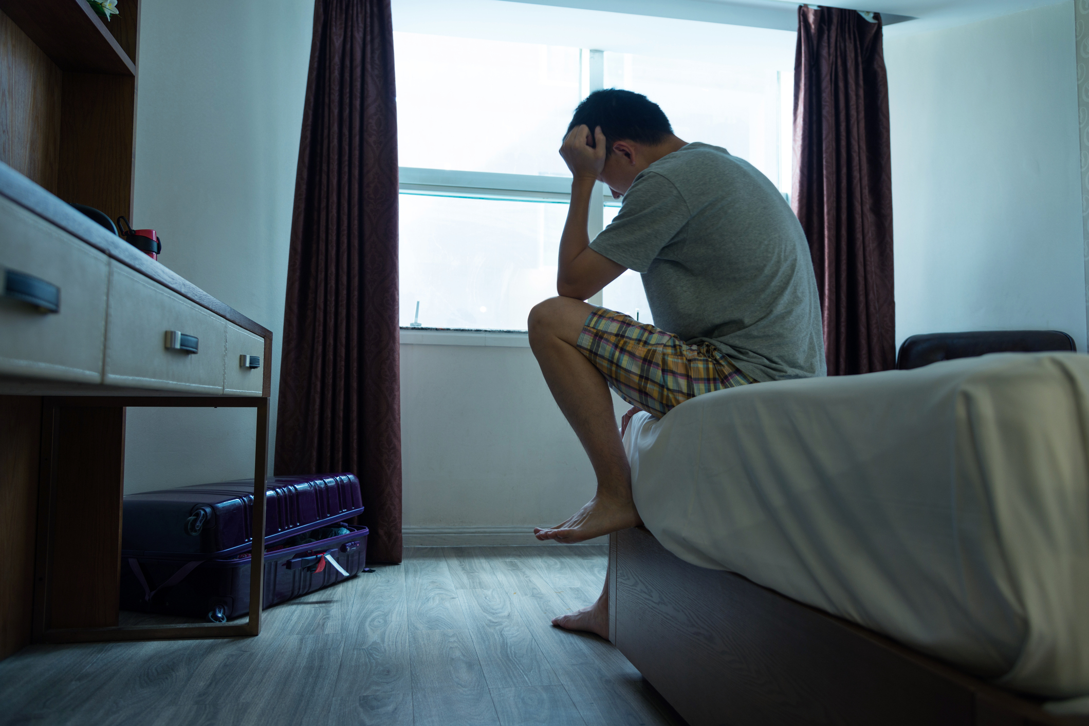 upset man sitting on the edge of his bed with his head in his hands