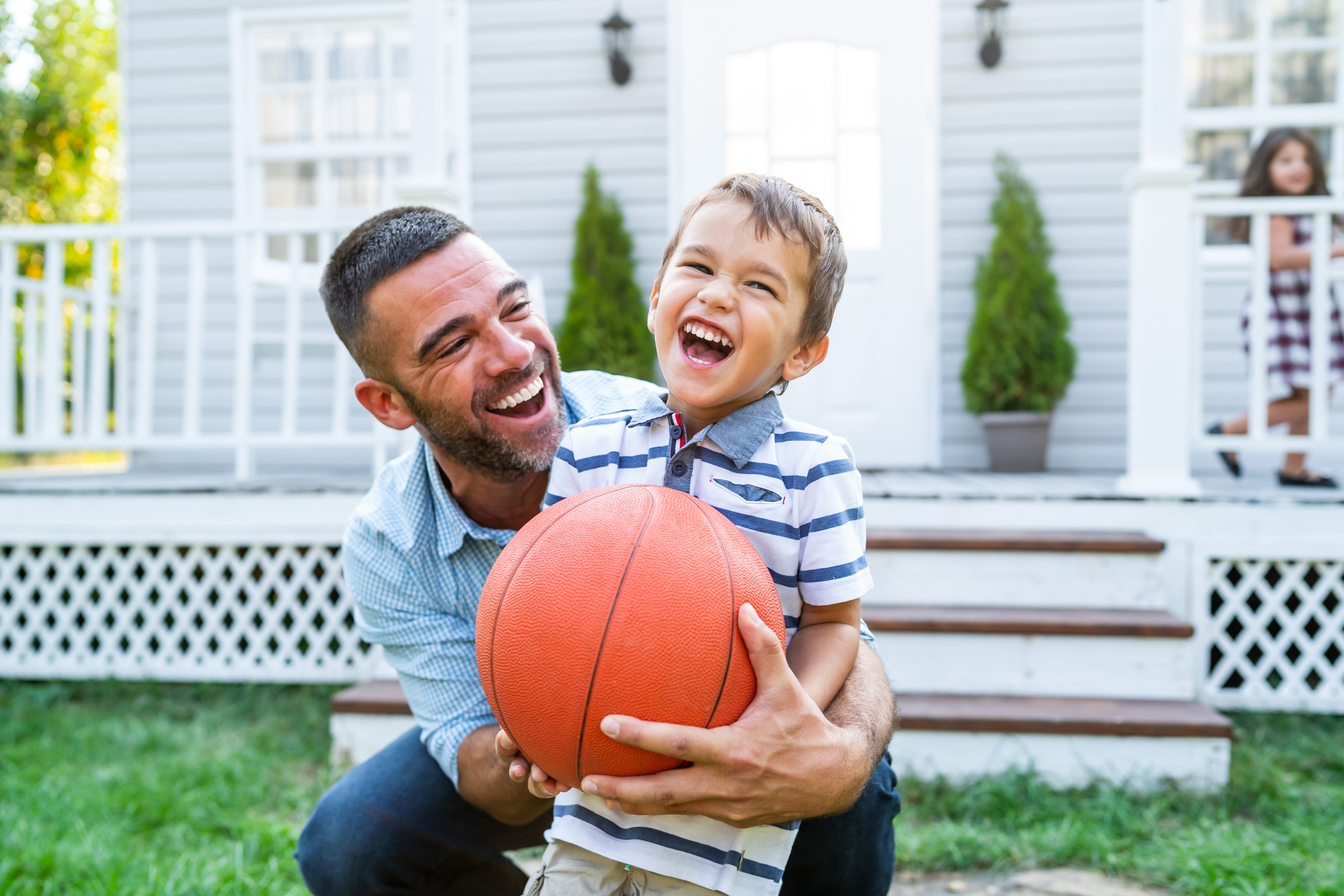 Father playing basketball with young step-son