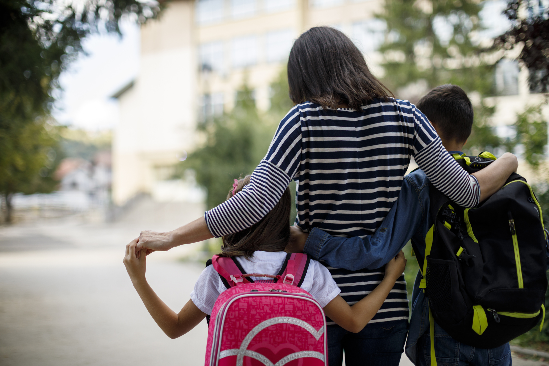Mother walking with both of her children arm in arm.