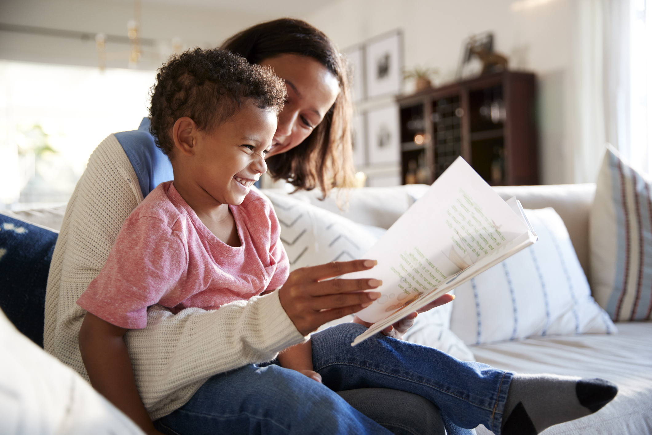 Mother sitting and reading with toddler son.