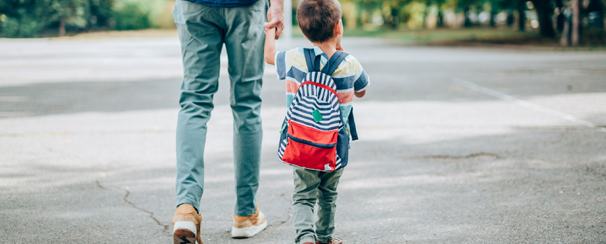 Dad walking holding young son's hand.