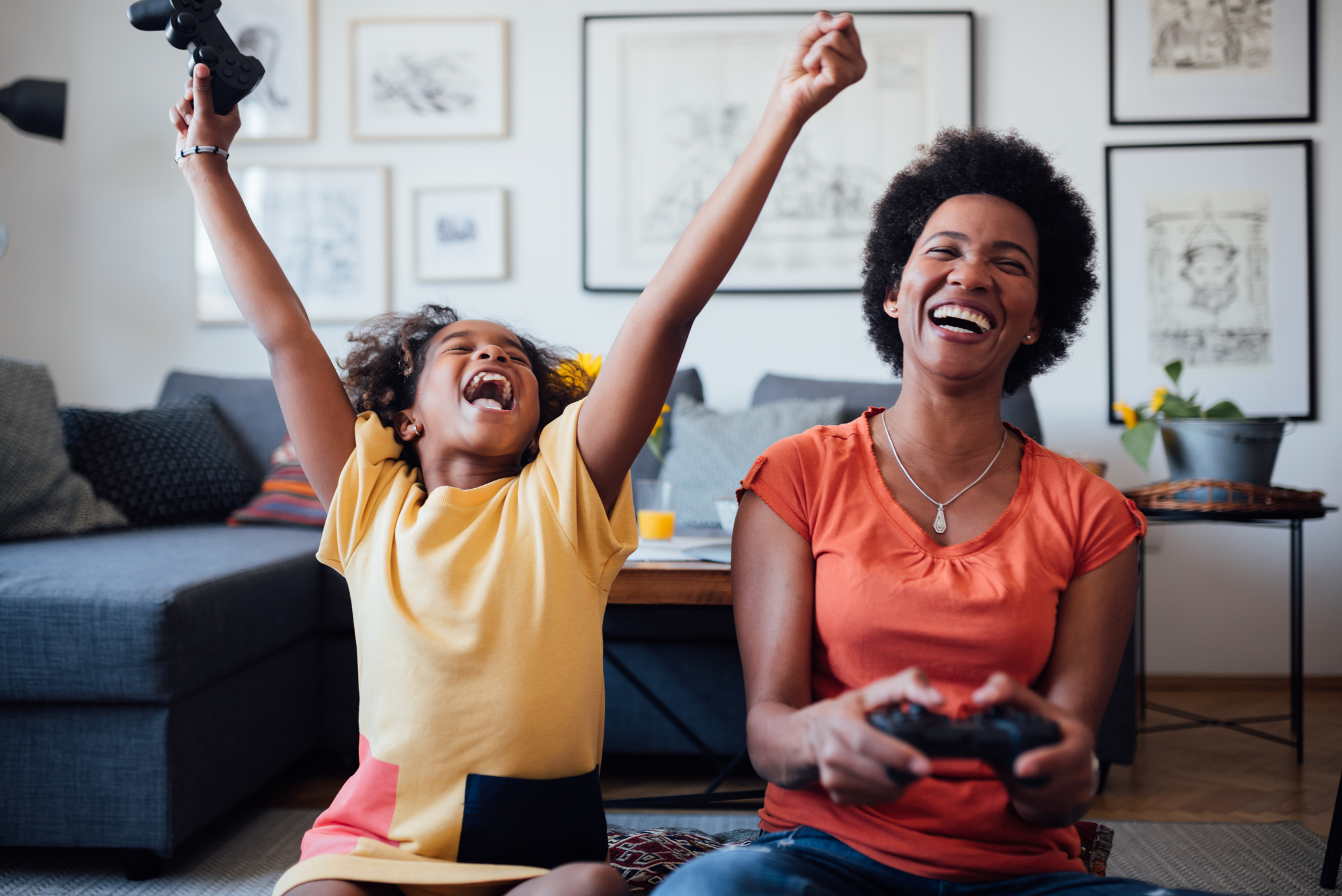 Joyful mom playing video games with young son