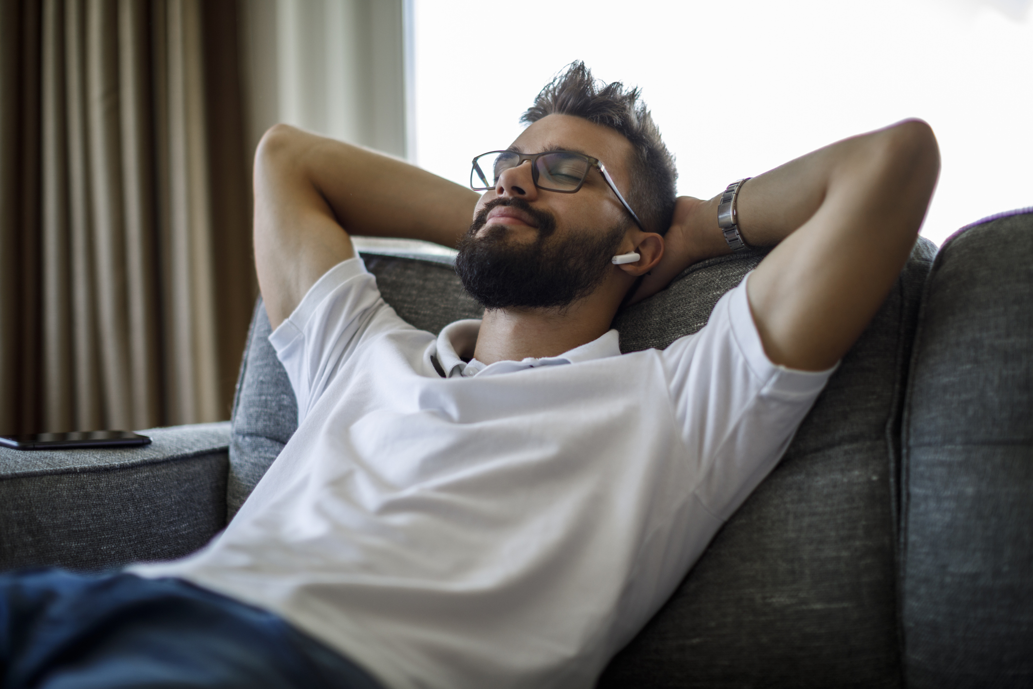 Man relaxing on couch listening to music