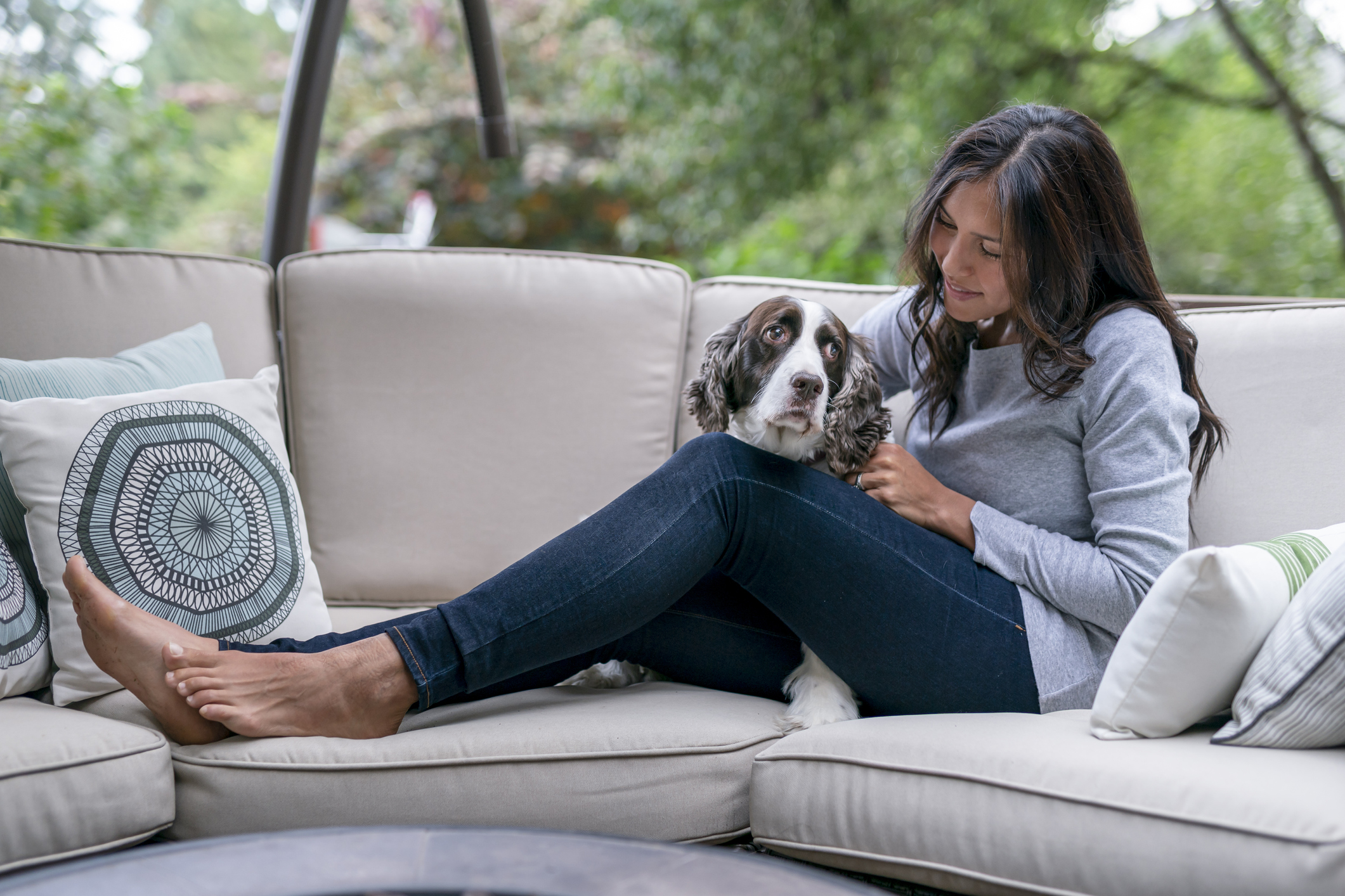 Woman lounging outside on coach with her dog