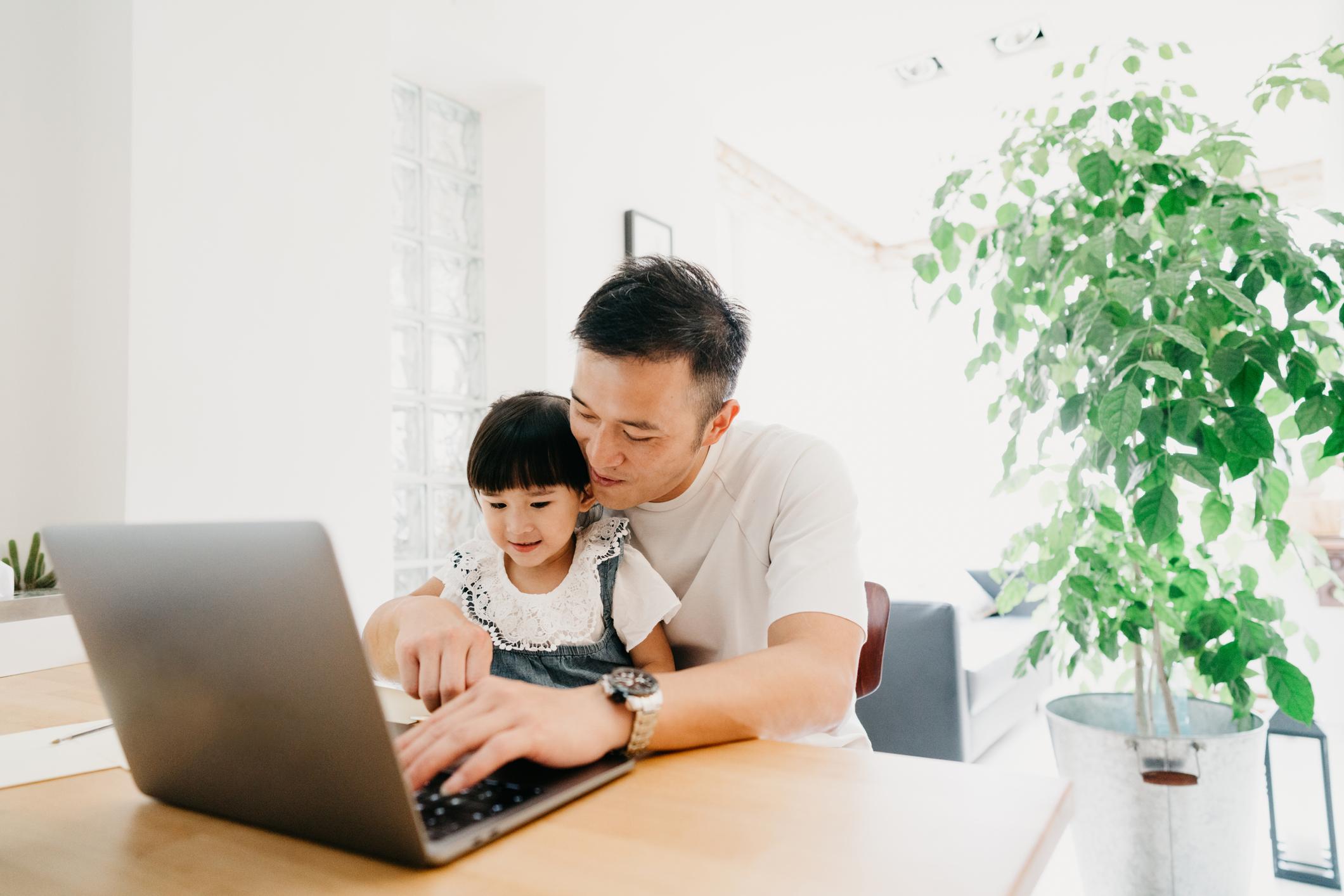 Dad teaching daughter to type on laptop
