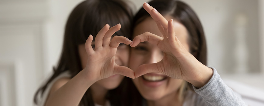 Mom and daughter making heart shape with joined hands