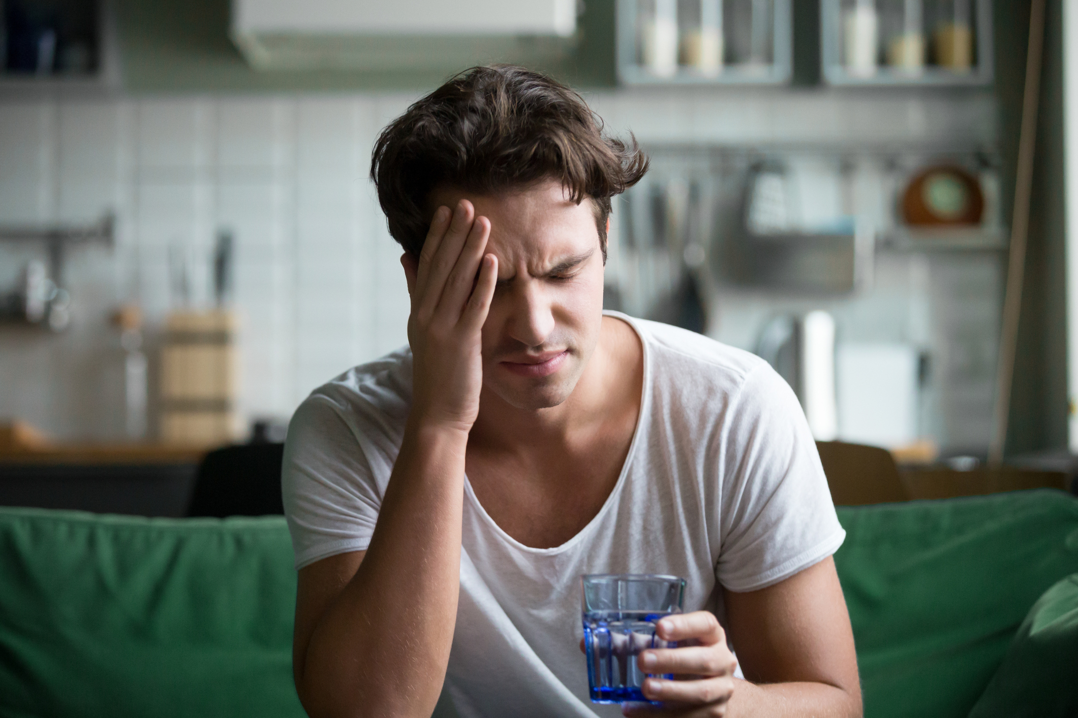 Man hungover with headache, drinking water.