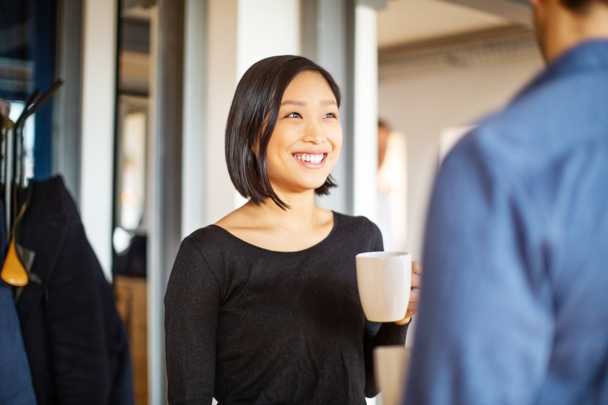 Woman having coffee with co-worker in office.