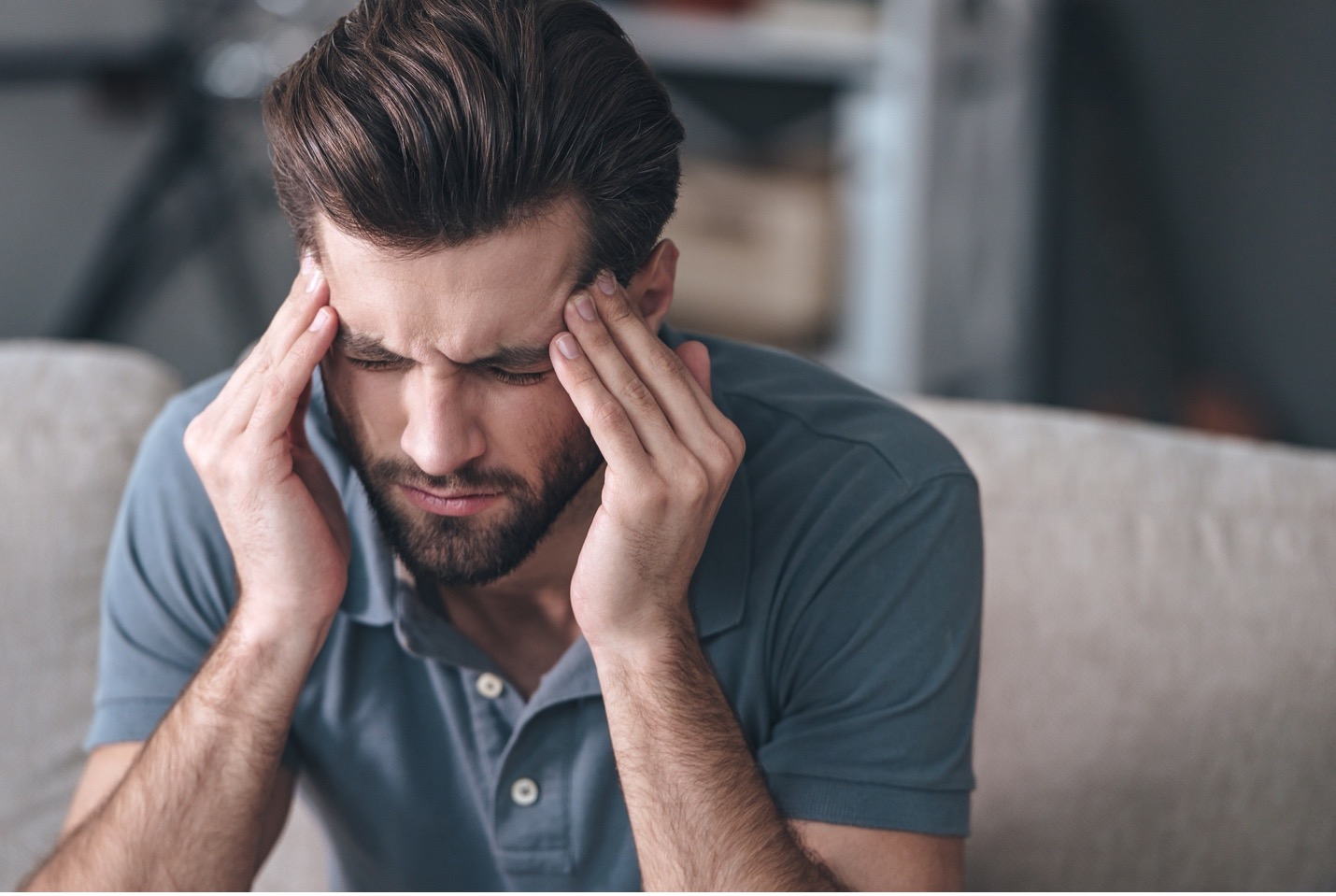 man with hands on the side of his head looking upset