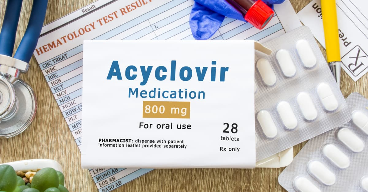 Packaging of drugs labeled Acyclovir medication is on doctor table with stethoscope