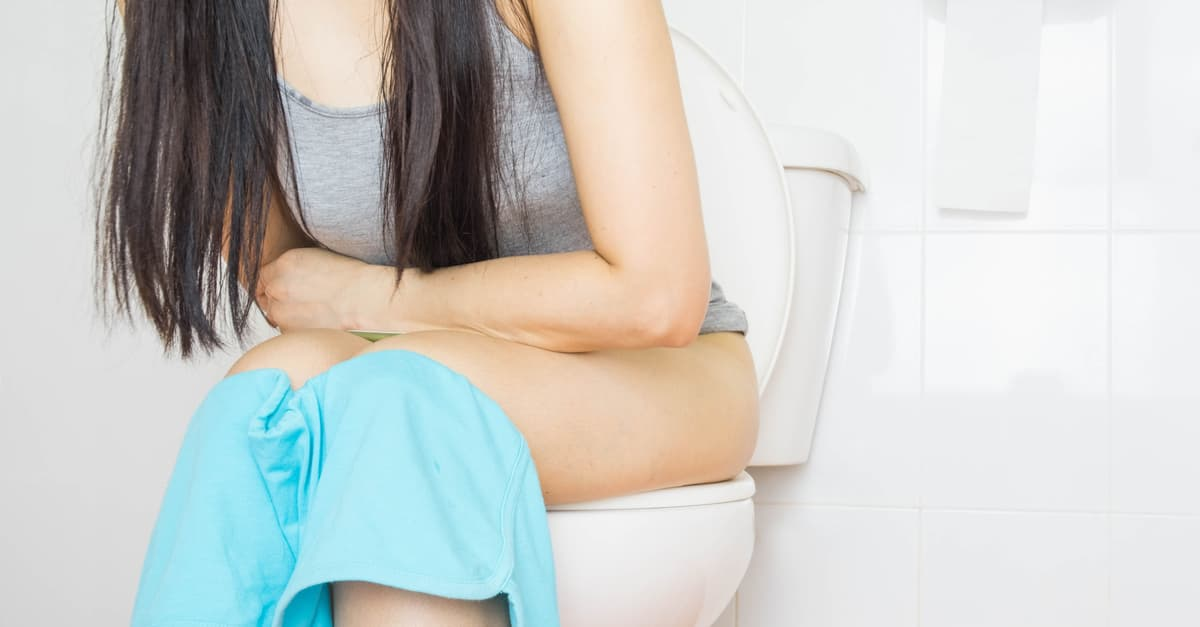 Woman sitting on the toilet having difficulty urinating
