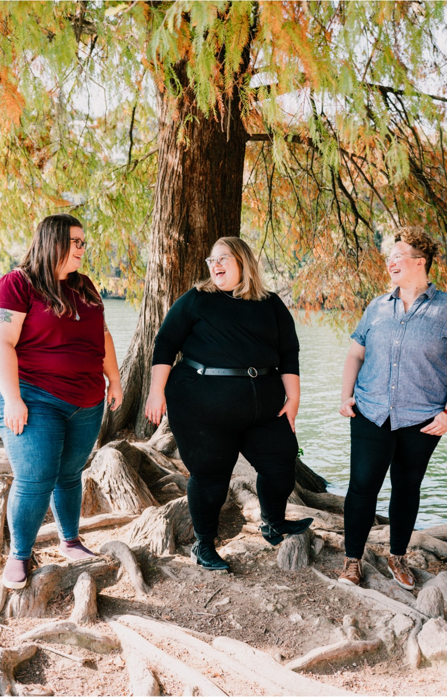 Three Ample + Rooted team members laughing together while standing at water's edge