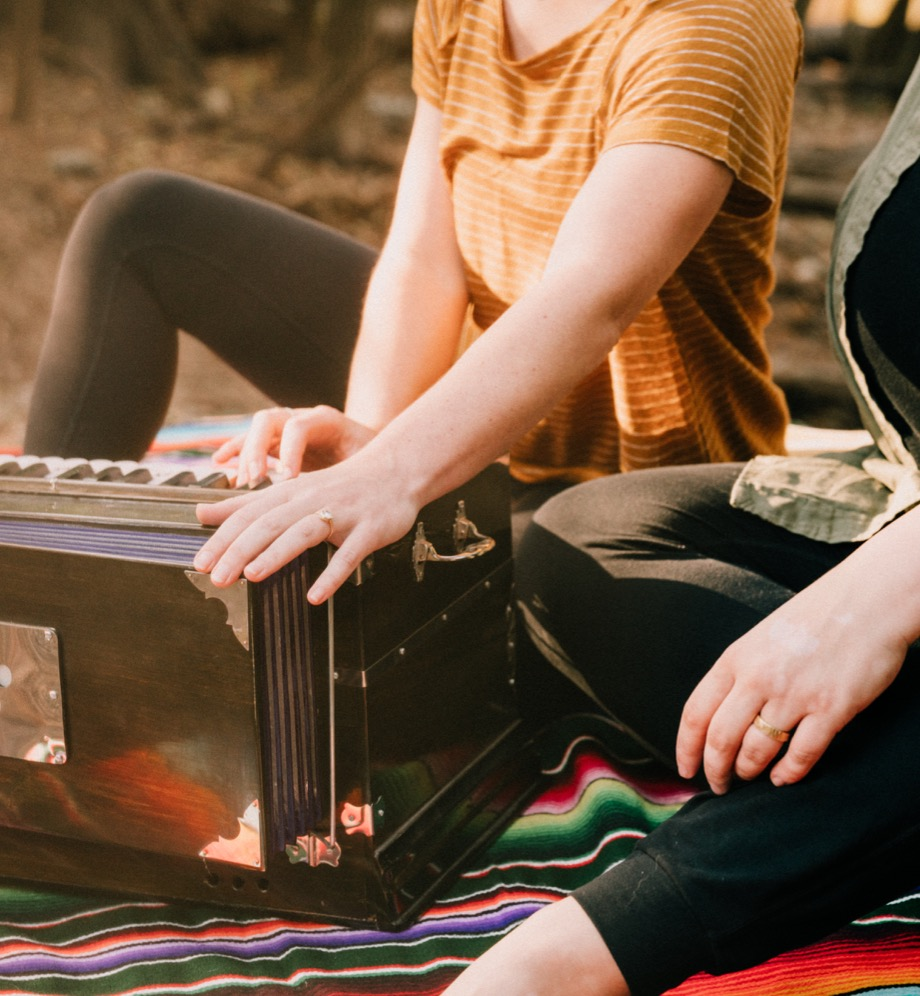 People sitting on a colorful blanket with a musical instrument that looks like an accordion