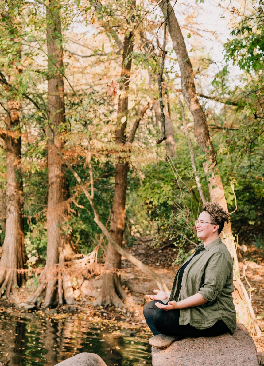 Neathery Thurmond meditating in lotus pose near the water and surrounded by trees