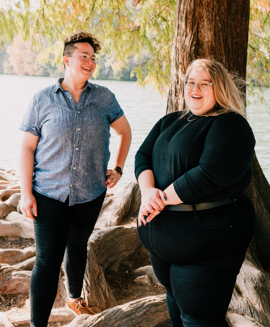 Neathery and Alison smiling and standing near the edge of a body of water and a tree