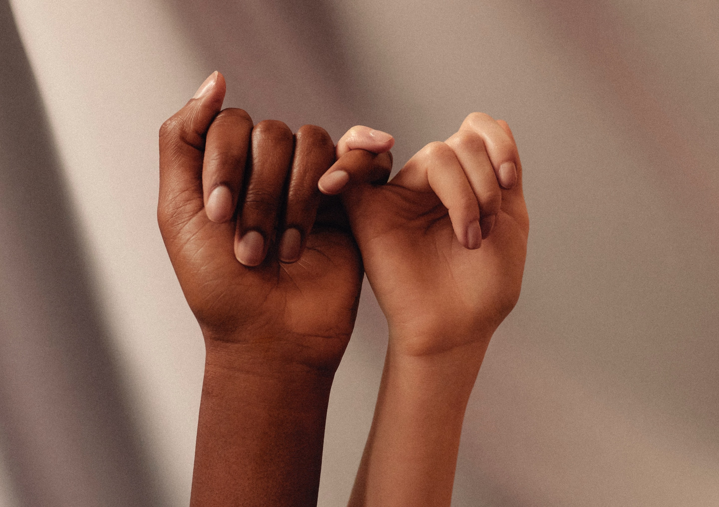 One darker and one lighter skinned hands making a pinkie promise gesture