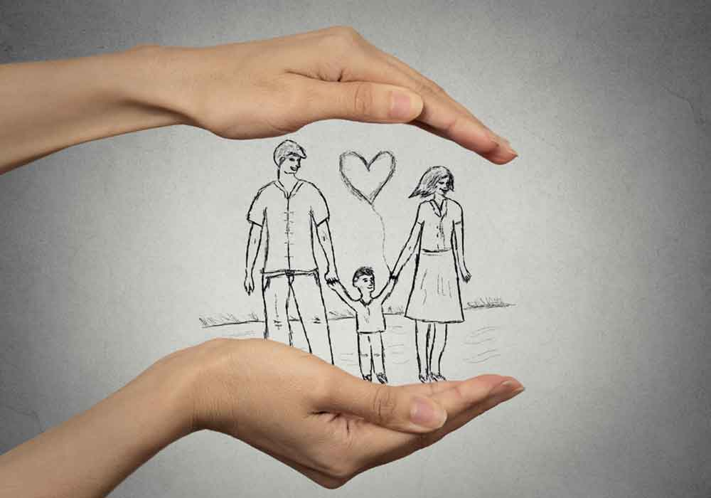 Woman's hands protecting a drawing of a happy family