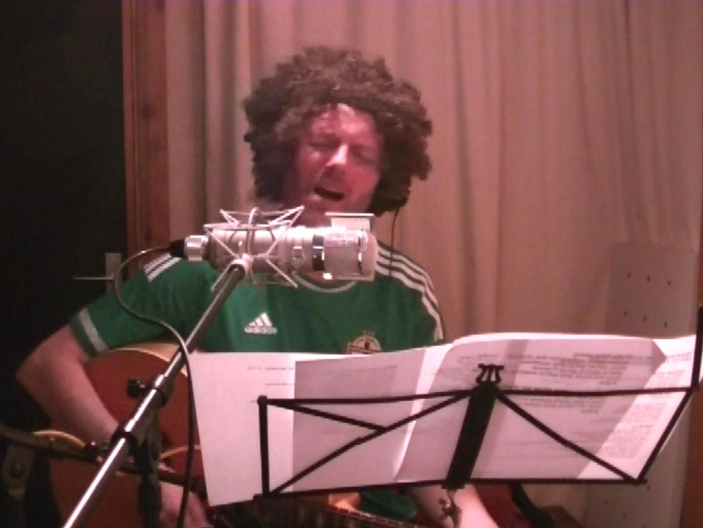 Steve singing and wearing a big wooly wig