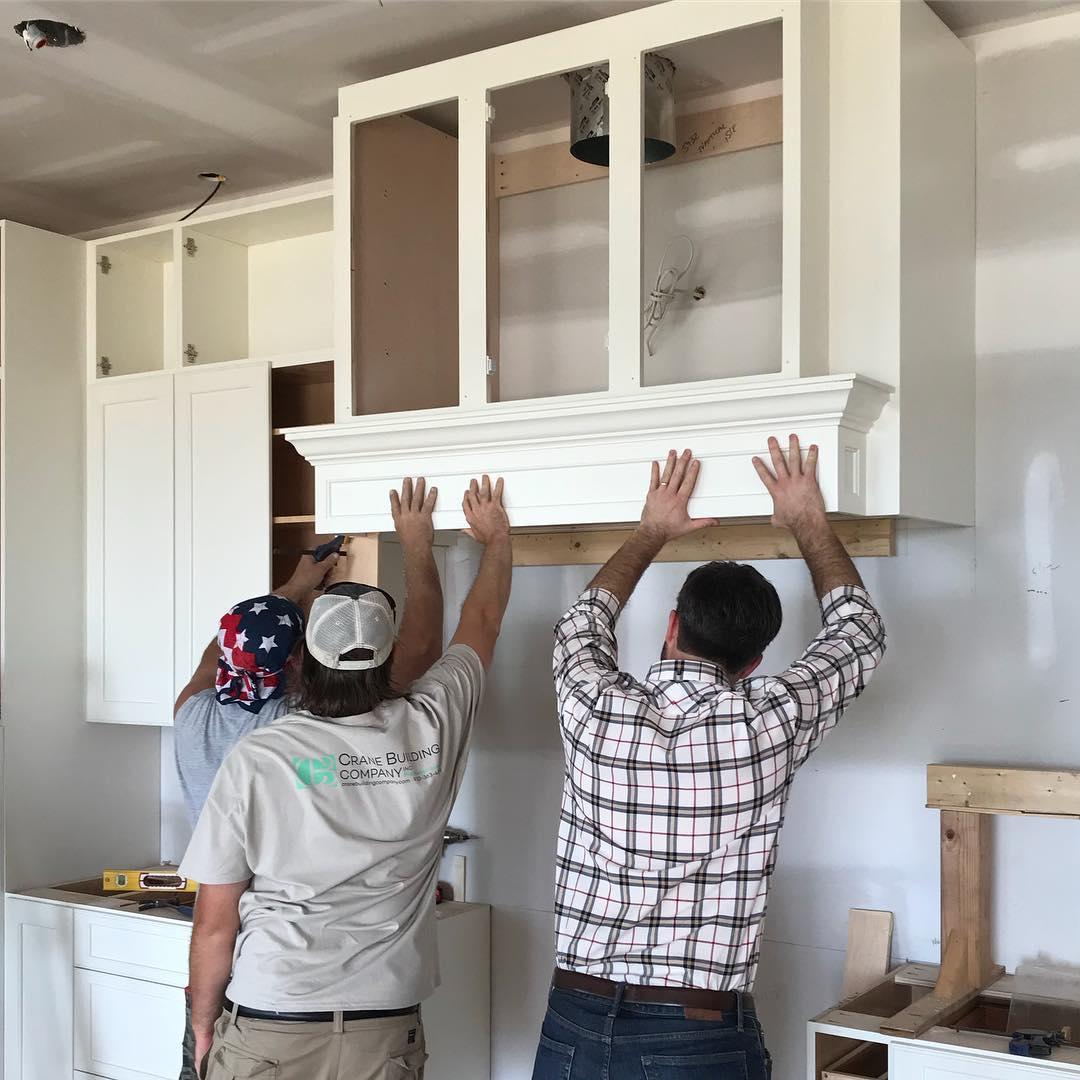 Men installing cabinet
