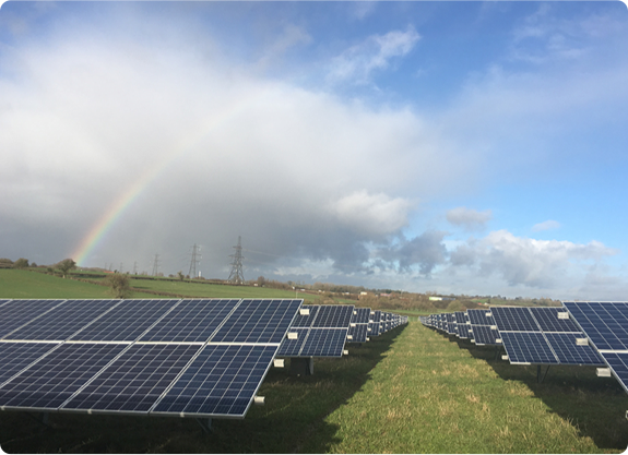 A large plot of solar panels in a green field with a rainbow in a cloudy sky.