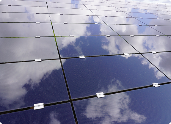 Close up of solar panels with the clouds reflected on their surface.