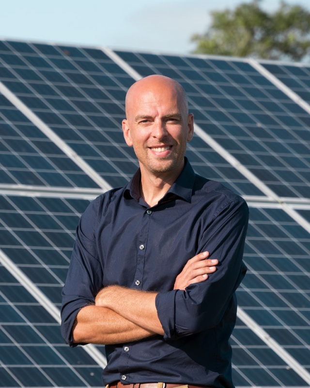 John Davies standing in front of a set of solar panels on a sunny day.
