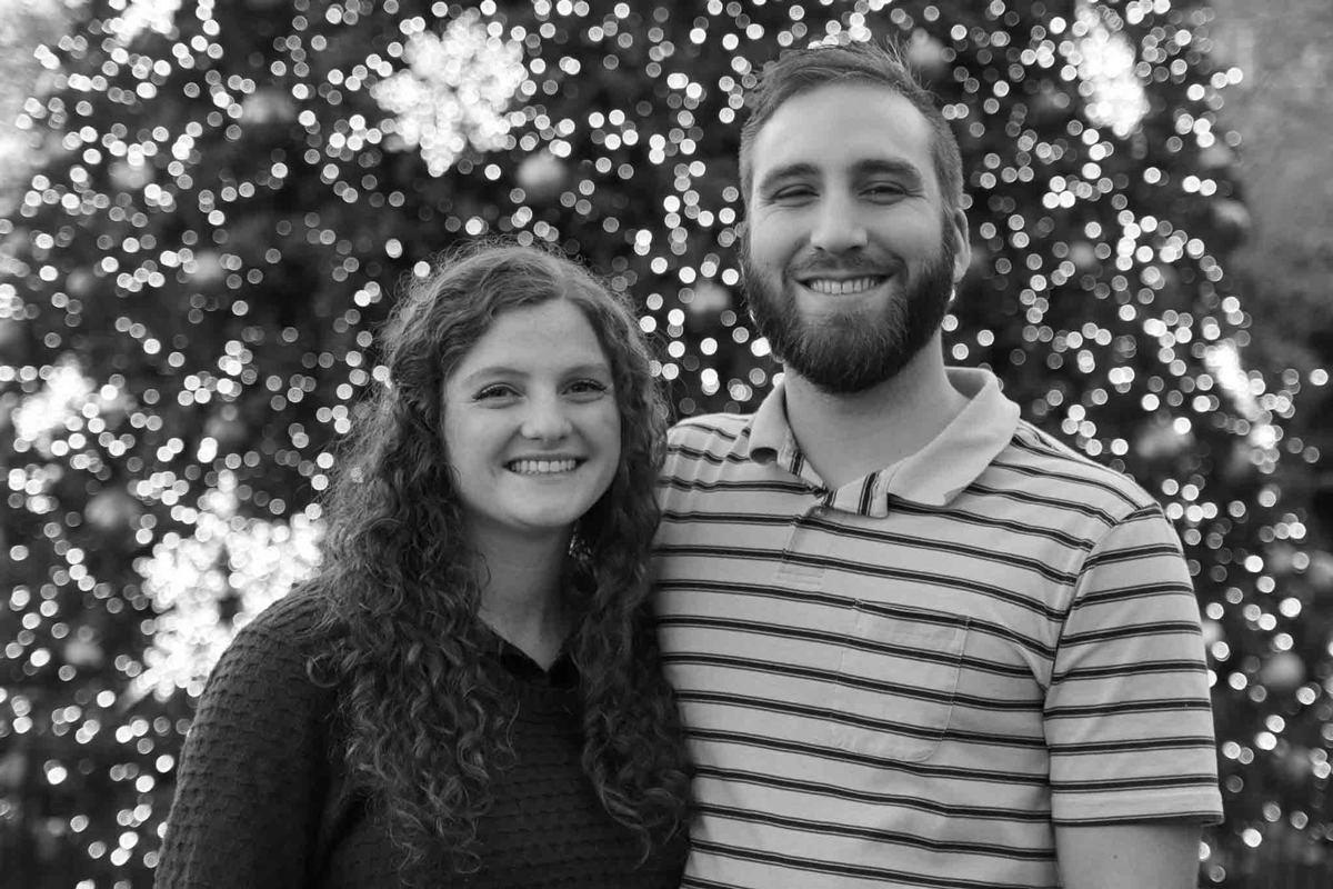 A couple posing in front of a Christmas tree.