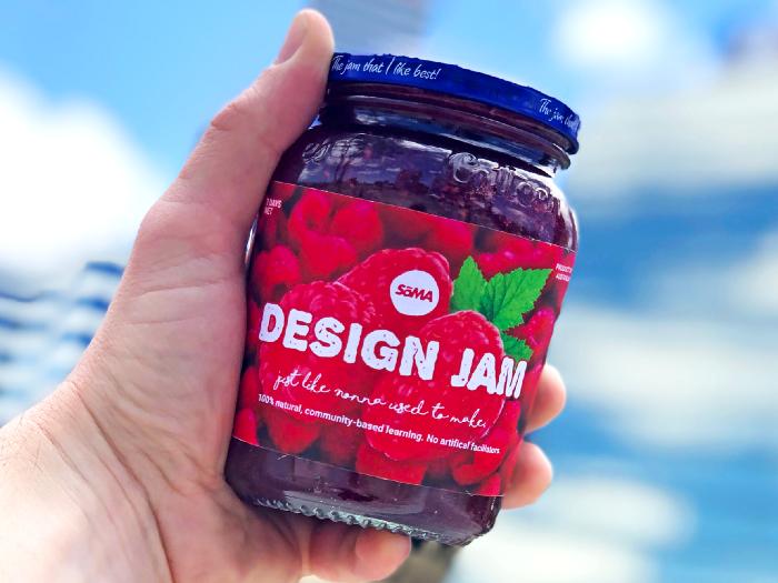 Hand holding a jam jar promoting Design Jam Bootcamp