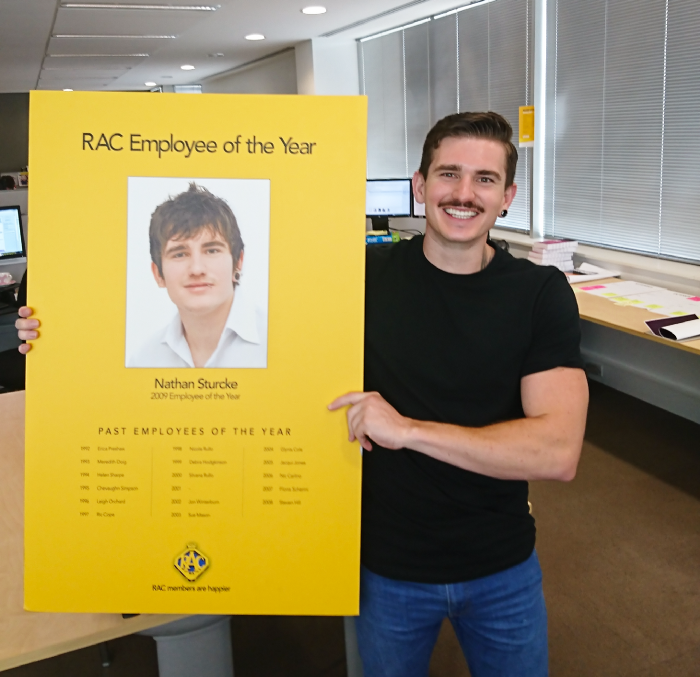 Nate Strucke holding a picture of him at RAC as Employee of the Year