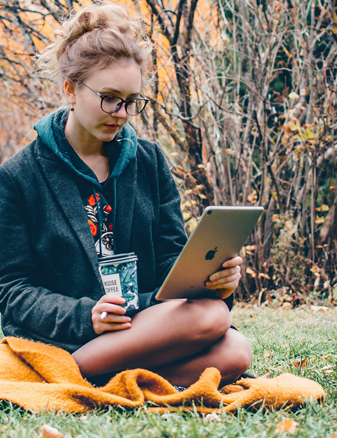 Girl using WiFi from Skyhook Solar Station to power iPad outside