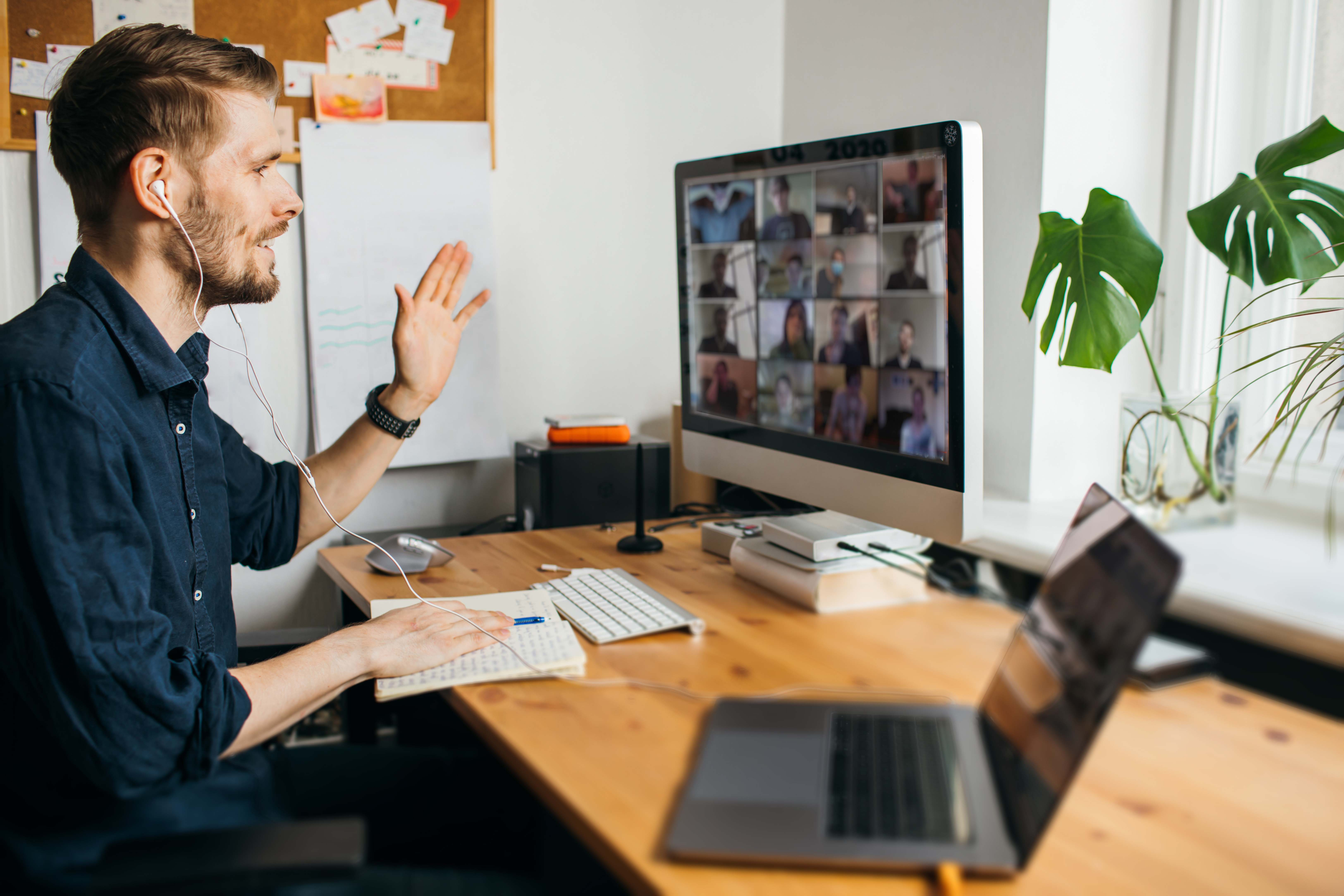 Man in a home office waves at co-workers on a video call.