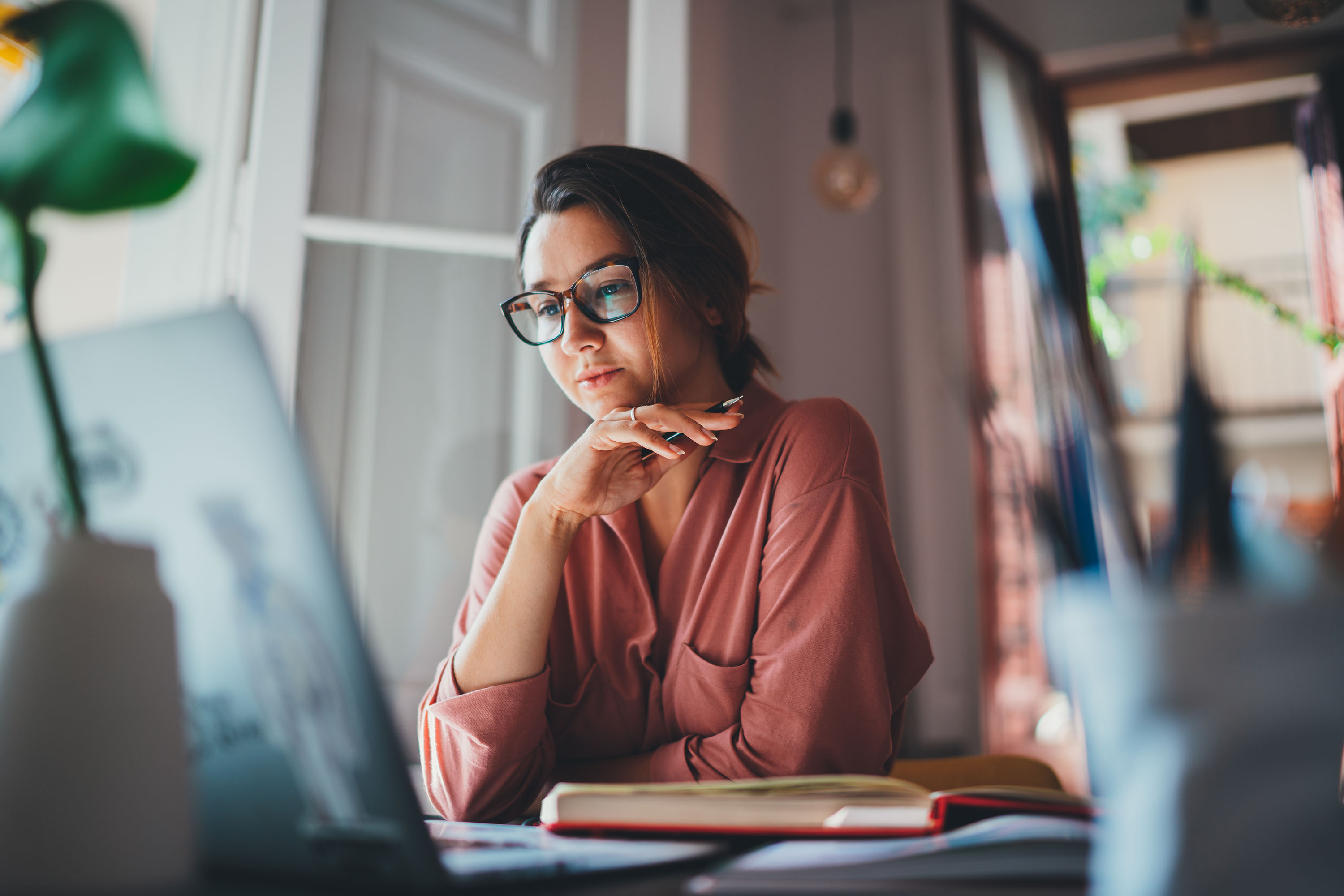 Lady with trendy glasses sits at her home workspace with a laptop.