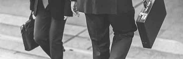 zwei personen in anzug und mit aktenkoffer begegnen sich