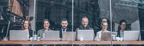 sechs menschen sitzen mit laptop in einer reihe und arbeiten gemeinsam