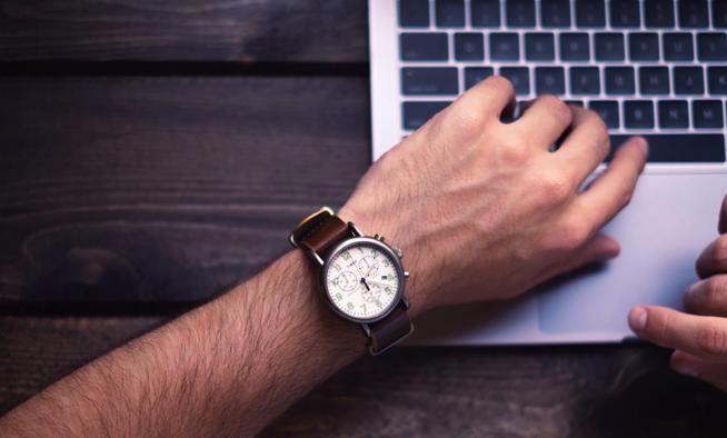 analoge armbanduhr an maennlichem handgelenk zeigt die zeit