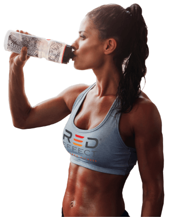A woman drinking form a water bottle after a workout