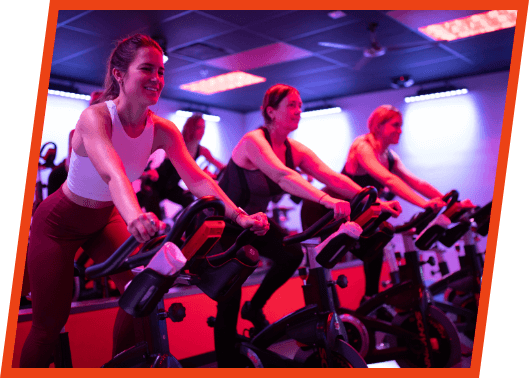 A group of Red Effect members riding spin bicycles during a class