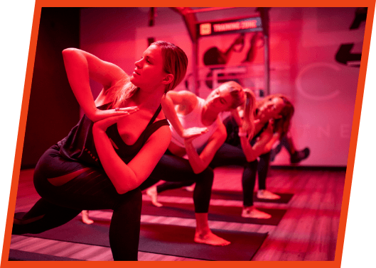 Women holding a yoga pose in a group class