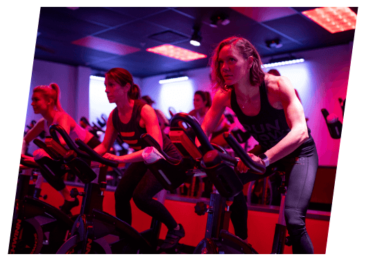 A group class with members exercising on stationary bicycles