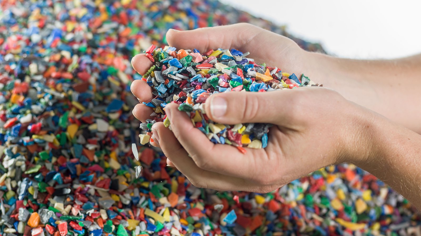 person holding shredded plastic bits