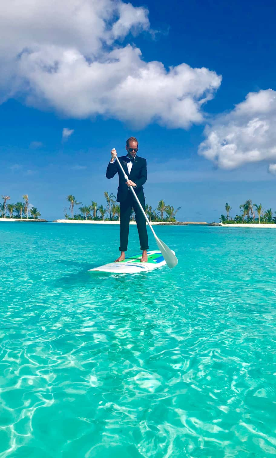 Garrett stands on a paddle board in the Maldives.