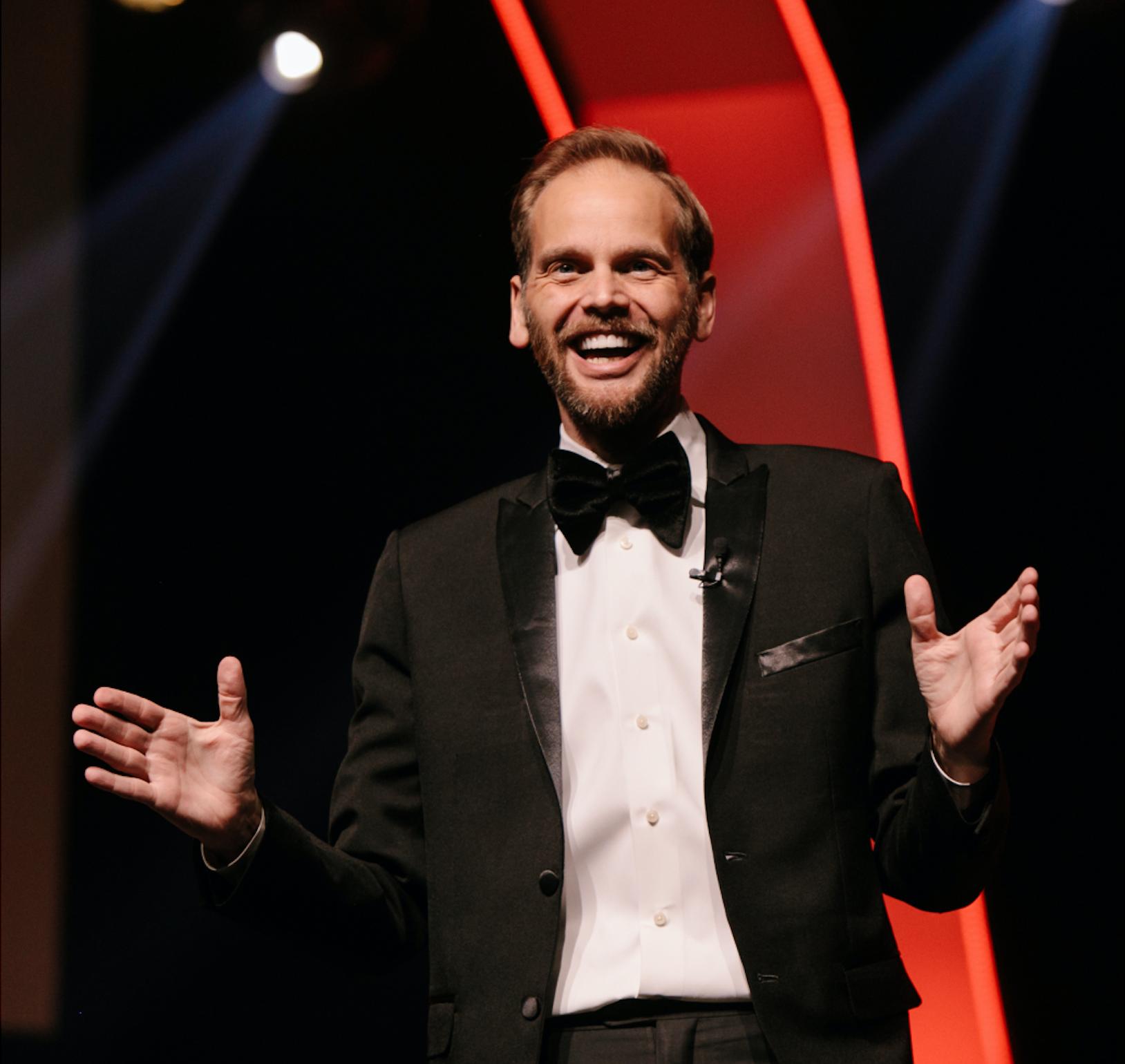 Garrett Gravesen speaking on a stage, dressed in a tuxedo.