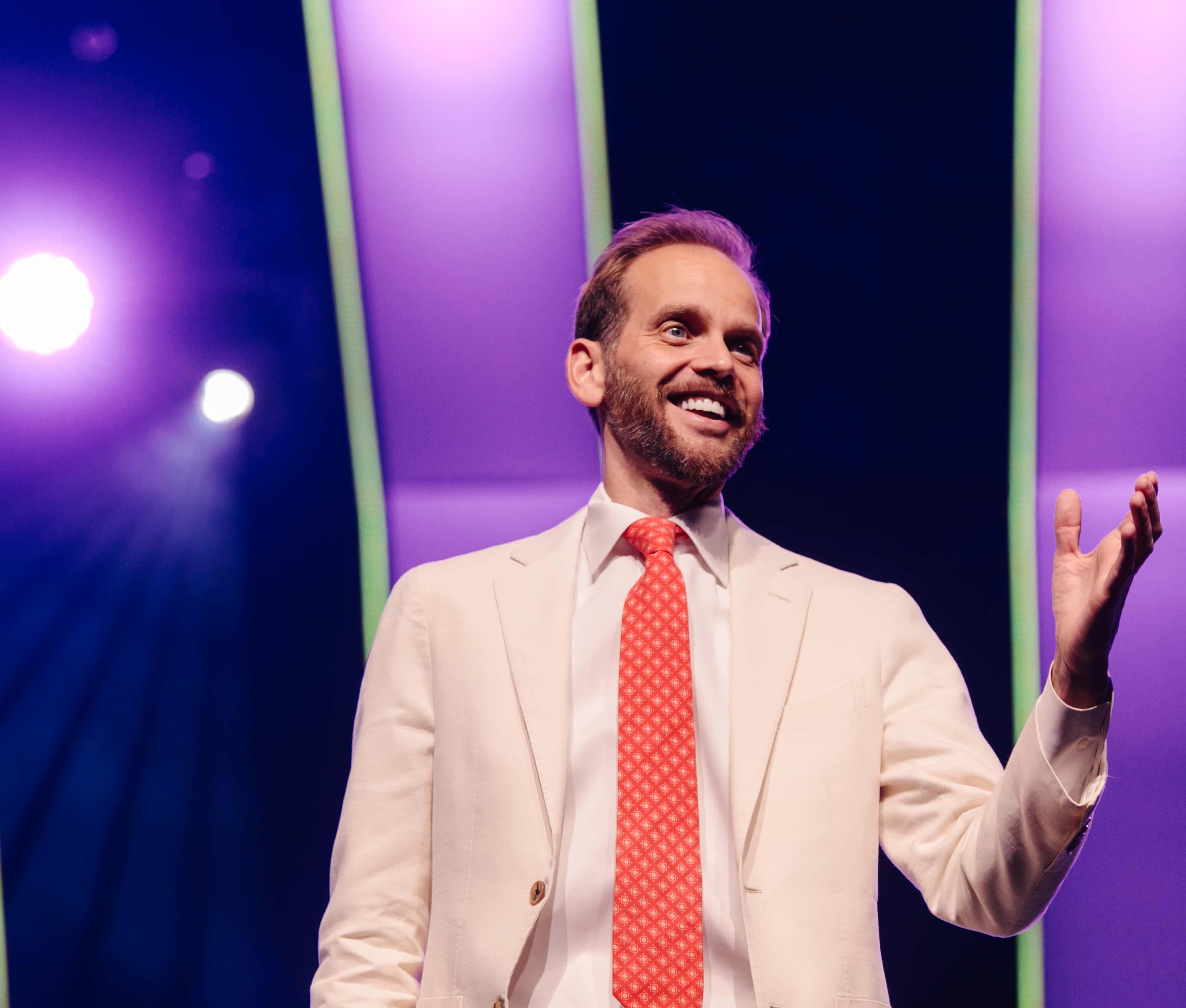 Garrett Gravesen speaking on a stage.